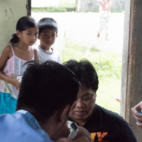 Village children look on as Erin prepares a vaccine