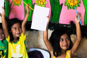 children hold up their new books and pens