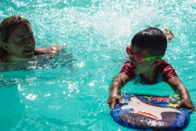 A boy wearing googles and holding a float